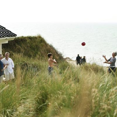 Family-Playing-Beach-Summerhouse