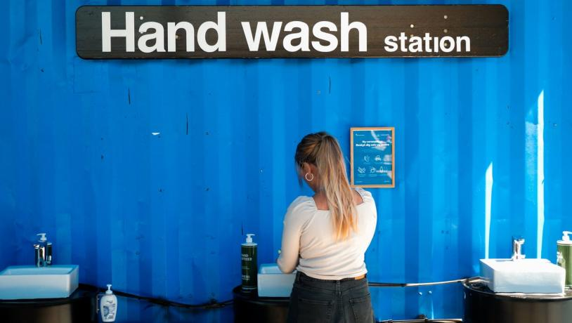 A woman washes her hands at a coronavirus handwash station