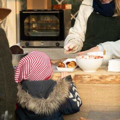A child buying æbleskiver at a stall at the Open Air Museum in North Sealand.